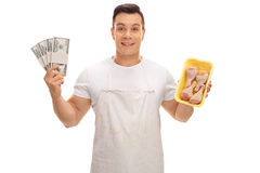 Butcher holding stacks of money and chicken drums Royalty Free Stock Image