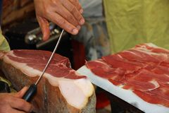 Butcher knife cut large slices of  ham to sell Stock Image
