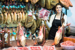 Butcher with lard and meat in counter of store Stock Images