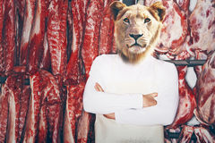 Butcher with a lion head with arms folded standing in front of red meat  Royalty Free Stock Photos