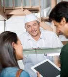 Butcher Looking At Couple Using Digital Tablet Royalty Free Stock Photo