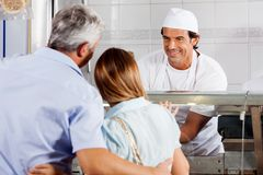Butcher Looking At Customers In Shop Royalty Free Stock Image