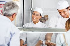 Butcher Looking At Male Customer Royalty Free Stock Photos