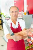 Butcher with machete in one hand and long bladed knife in other Royalty Free Stock Image