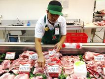 A butcher at a meat section of a grocery store Stock Image