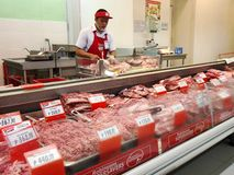 A butcher at a meat section of a grocery store Royalty Free Stock Photos