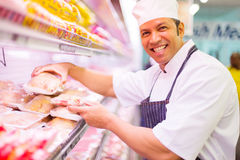 Butcher organizing meat products Stock Image
