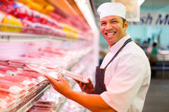 Butcher organizing meat products Royalty Free Stock Images