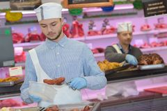 Butcher packaging cooked sausage Stock Image