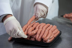 Butcher packing raw sausages. Close-up of butcher packing raw sausages at meat factory Royalty Free Stock Photography