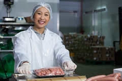 Butcher packing raw sausages. Portrait of female butcher packing raw sausages at meat factory Stock Images