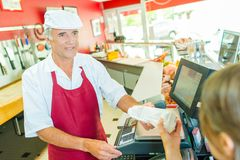 Butcher passing package to customer royalty free stock photo