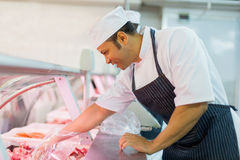 Butcher picking piece meat Stock Image