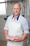 Butcher posing with lumps of meat Stock Photos