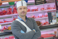 Butcher posing in shop Stock Image