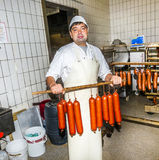 Butcher prepares fresh sausage Royalty Free Stock Images