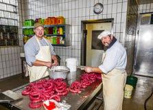 Butcher prepares fresh sausage Stock Image