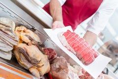 Butcher preparing customer`s order stock images