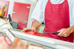 Butcher preparing cut beef in shop. Butcher preparing a cut of beef in his shop stock photography