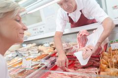 Butcher preparing cut meat. Butcher preparing a cut of meat royalty free stock images