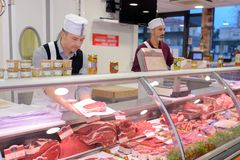 Butcher preparing meat behind counter stock images
