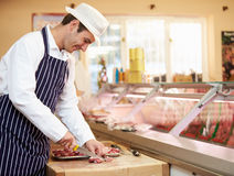 Butcher Preparing Meat In Shop. Smiling away From Camera Royalty Free Stock Photos