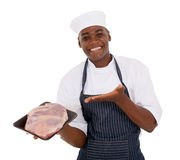 Butcher presenting fresh meat. Cheerful young african butcher presenting fresh meat Royalty Free Stock Photo
