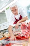 Butcher reaching into counter stock images