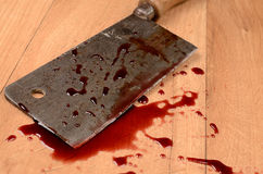 Butcher's cleaver. With blood on a wooden floor stock photography