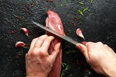 Butcher`s hands ready to cut with a knife raw pork tenderloin fillet.  stock photography