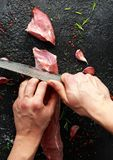 Butcher`s hands ready to cut with a knife raw pork tenderloin fillet.  royalty free stock photo