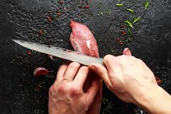 Butcher`s hands ready to cut with a knife raw pork tenderloin fillet.  royalty free stock photos