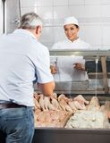 Butcher Selling Chicken Meat To Customer Stock Images