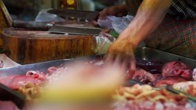 Butcher selling fresh meat in local Asian market stock footage