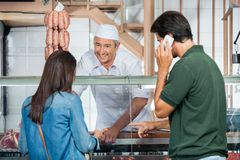Butcher Selling Meat To Couple In Butchery. Happy mature butcher selling meat to couple in butchery Stock Photography