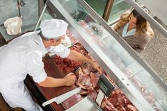 Butcher Selling Meat To Customer At Display Royalty Free Stock Photo