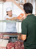 Butcher Selling Meat To Male Customer Stock Image