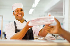 Butcher selling packed meat. Friendly male butcher selling packed meat to customer in butchery Royalty Free Stock Images