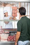 Butcher Selling Sausages To Customer At Shop Stock Photos