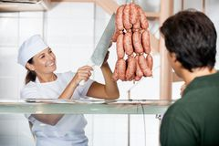 Butcher Selling Sausages To Male Customer Royalty Free Stock Image