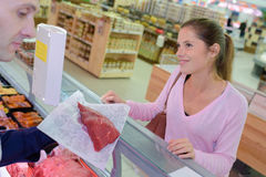 Butcher serving customer beef in supermarket Royalty Free Stock Photos