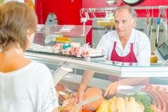 Butcher serving customer at deli counter Royalty Free Stock Image