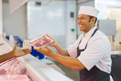 Butcher serving customer. Happy middle aged butcher serving customer in butchery Royalty Free Stock Images