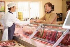 Butcher Serving Customer In Shop Stock Image