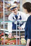 Butcher Serving Customer In Shop Royalty Free Stock Images