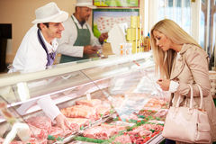 Butcher Serving Customer In Shop stock images