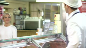 Butcher Serving Customer In Shop. Woman asks butcher about selection of meat on display before selecting her purchase.Shot on Sony FS700 in PAL format at a frame stock video