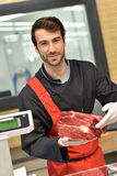 Butcher serving meat to customers Royalty Free Stock Image