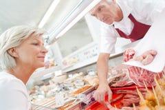 Butcher serving senior customer stock photography