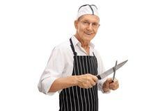 Butcher sharpening his knife. Elderly butcher sharpening his knife isolated on white background stock photos